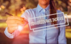Woman in a blue business shirts holding a pen and pointing on a word conversion rate increase